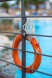 Boya de vida anaranjada con la cuerda cerca de la piscina que cuelga en el puente fotos de archivo