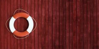 Boya de vida roja y blanca en el lado de una nave de madera Imágenes de archivo libres de regalías