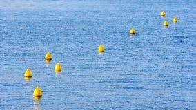 Boyas amarillas en el agua imágenes de archivo libres de regalías