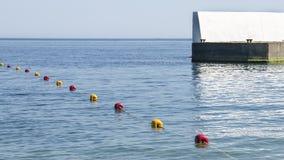 Boyas amarillas y rojas en el mar cerca del embarcadero Imagen de archivo
