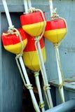 Boyas rojas y amarillas del muelle resistido foto de archivo