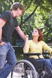 Boyfriend. Boy is talking to his girlfriend on a wheelchair Royalty Free Stock Photo