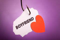 Boyfriend. Piece of paper with boyfriend pierced on hook on colored background Stock Image