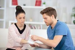 Free Boyfriend Applying Arm Bandage To Girlfriend Royalty Free Stock Images - 102663359