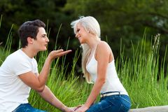 Boyfriend blowing kiss to young woman outdoors. Stock Photo