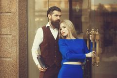 Boyfriend with bottle of wine hugging girlfriend at glass door. Woman or girl in blue dress and men hipster outdoors on brick wall. Alcohol and convive. Couple royalty free stock image