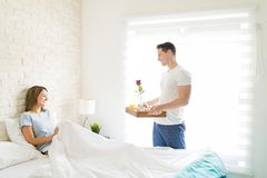 Boyfriend Bringing Tray With Breakfast For Woman In Bed. Happy boyfriend bringing tray with breakfast for women in bed at home Royalty Free Stock Image