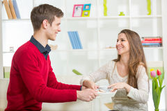The boyfriend brings his girlfriend on a tray coffee and cookies Royalty Free Stock Photography