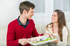 The boyfriend brings his girlfriend on a tray coffee and cookies Stock Photo