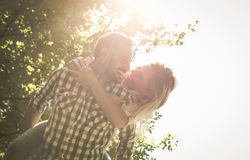 Boyfriend carries the girl on her back with open arms. Stock Photography