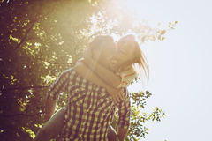 Boyfriend carries the girl on her back with open arms. Stock Photos