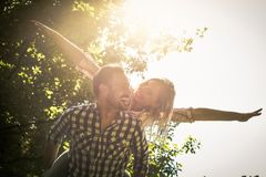 Boyfriend carries the girl on her back with open arms. Happy co royalty free stock photography