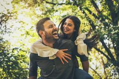 Boyfriend carrying his girlfriend on piggyback. Portrait. Boyfriend carrying his girlfriend on piggyback. Moving activity royalty free stock photo