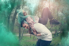 Young couple in outdoor. Boyfriend carrying his girlfriend on his piggyback Stock Photo