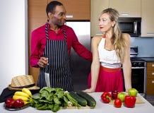 Boyfriend Cooking for Spouse. Sweet helpful boyfriend cooking for girlfriend at home Stock Image