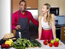 Boyfriend Cooking for Spouse. Sweet helpful boyfriend cooking for girlfriend at home Stock Photography