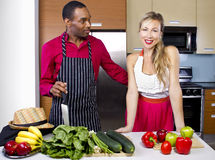 Boyfriend Cooking for Spouse. Sweet helpful boyfriend cooking for girlfriend at home Royalty Free Stock Photos