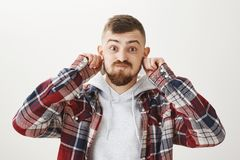 Boyfriend cover flesh tunnels so girlfriend would not pull them. Portrait of funny emotive young guy with stylish. Haircut and beard holding hands on ears Stock Images