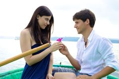 Boyfriend donating pink flower to girlfriend in love Royalty Free Stock Image