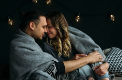Boyfriend and girfriend touching each other sitting on bed with grey blankets and pillows. Cozy room with lights royalty free stock photos
