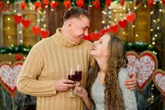 Boyfriend and girlfriend drinking wine on valentine`s day. Boyfriend and girlfriend celebrate valentine`s day. they hugging, smiling and drinking wine. Concept royalty free stock images