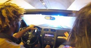 Boyfriend and girlfriend driving through motorway tunnel stock footage