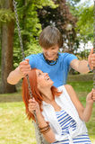 Boyfriend and girlfriend enjoying date on swing Stock Photo