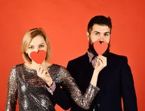 Boyfriend and girlfriend have date. Couple in love holds hearts. On red background. Girl and bearded men with hidden faces play with paper hearts covering mouth royalty free stock photos