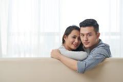 Boyfriend and girlfriend. Hugging Vietnamese boyfriend and girlfriend sitting on sofa royalty free stock photography