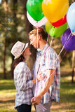 Boyfriend and girlfriend. Lovely teen boyfriend and girlfriend with helium balloons in forest stock images