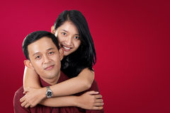 Boyfriend and girlfriend over red copy space. Young men hugged by his girlfriend, on red background with copy space Royalty Free Stock Images