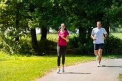 Boyfriend and girlfriend running a race outdoors Stock Photo