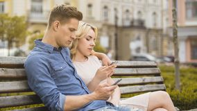 Boyfriend and girlfriend sitting on bench, engrossed in phones, networking Stock Photos