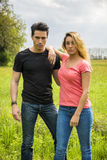 Boyfriend and girlfriend standing showing romantic love. Boyfriend and girlfriend standing in countryside in green luscious field, embracing each other and Royalty Free Stock Image