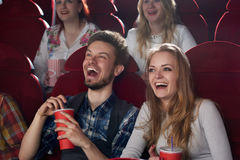 Boyfriend and girlfriend surprised smiling watching comedy movie at cinema. Royalty Free Stock Photos