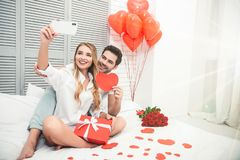 Boyfriend and girlfriend taking selfie. Together on smartphone in the bed, valentines day concept stock photography