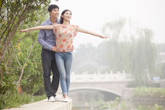 Boyfriend and Girlfriend Walking by a Canal, Arms Outstretched Royalty Free Stock Photography