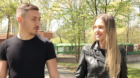 Boyfriend and girlfriend walking in park. Happiness and relationship. Young inlove couple stock footage