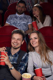 Boyfriend and girlfriend watching comedy at cinema together with friends. Royalty Free Stock Photos