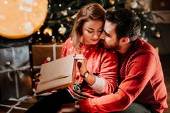boyfriend giving a Christmas present to his girl, enjoying holidays together royalty free stock image