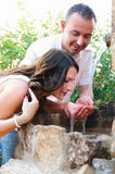 Boyfriend giving drink to his girlfriend in a fountain Royalty Free Stock Images
