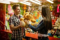 Boyfriend giving gift his girlfriend on amusement park. Smiling boyfriend giving gift his girlfriend on amusement park stock photos