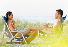 Boyfriend giving girlfriend foot massage at beach Royalty Free Stock Photos
