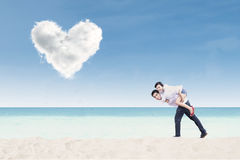 Boyfriend giving piggyback ride under heart cloud Royalty Free Stock Image