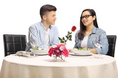 Boyfriend giving a red rose to a girlfriend at a restaurant. Isolated on white background royalty free stock photos