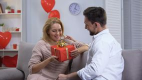 Boyfriend giving surprised happy lady gift for st Valentines day, happy couple stock video footage