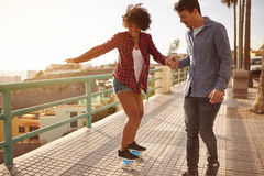 Boyfriend helping girl to keep her balance. Boyfriend showing girl how to skateboard while holding her hand tightly and walking her slowly while she has her Stock Photo