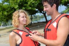 Boyfriend helping girlfriend button safety jacket Stock Photos