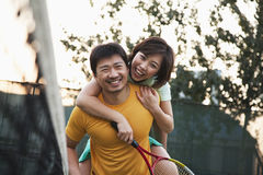 Boyfriend holding his girlfriend next to the tennis net Stock Photo