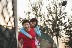 Boyfriend holding his girlfriend next to the tennis net Stock Photography